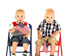 Two cute blond boys holding American flags sitting — Stock Photo
