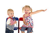 Cute boy and girl holding American flags cute expression — Stock Photo