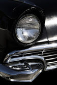 Classic sixties black car front headlight and grill — Stock Photo