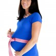 Happy pregnant woman showing off her belly with a pink bow — Stock Photo #50618101