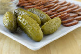 Cornichons and sausage on a white plate — Stock Photo