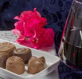 Chocolate flowers red wine glasses — Stock Photo