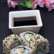 Canada sushi roll decorated with sakura on black background — Foto de Stock