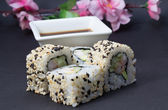 Canada sushi roll decorated with sakura on black background — Stock Photo