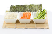 Rice salmon and sliced cucumber in white dish with nori on bamboo mat — Stock Photo