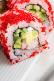 Sushi roll with red tobiko on white plate — Stock Photo