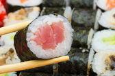 Tuna maki sushi roll in chopsticks — Stock Photo
