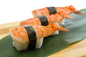 Shrimp sushi nigiri on wooden plate — Stock Photo