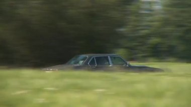 Car driving passed grassy field — Stock Video