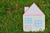 Paper house in the grass. — Stock Photo