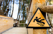 Slippery when wet - Wooden Sign in the Park — Stock Photo