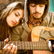 Romantic young Couple playing Guitar outdoor after the Rain — Stock Photo