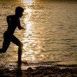 Silhouette of a Kid running over a Surfboard — ストック写真