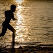 Stock Photo: Silhouette of a Kid running over a Surfboard