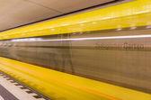 Yellow Train speeding behind metal Seats — Stock Photo