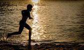 Silhouette of a Kid running over a Surfboard — Stok fotoğraf