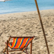 Deckchair and Parasol on a solitary Beach — Stock Photo