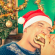 Portrait of an handsome young man with Santa hat eating cheeseburger — Stock Photo