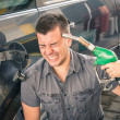 Young adult shooting himself over crazy petrol and fuel prices. — Stock Photo #33818895