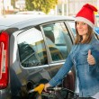 Young woman at gas station with Santa hat — Stockfoto
