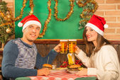 Happy Couple at restaurant with Santa hats — Stock Photo