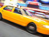 Yellow taxi speeding near Times Square in New York. — Foto Stock