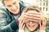 Young man covering the eyes of an happy surprised girlfriend — Stock Photo