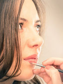 Make-up artist refining lips of a beautiful young Model — Stock Photo