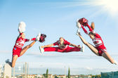 Cheerleaders team performing a Jump with male Coach — Stock Photo
