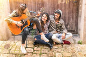 Teenagers best friends playing guitar outdoors — Stockfoto