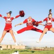 Cheerleaders team with male Coach performing synchronized jump — Stock Photo #41737913