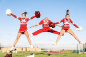 Cheerleaders team with male Coach performing a synchronized jump — Stock Photo