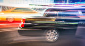 Speeding car and taxi cab in the night traffic of New York City — Stock Photo