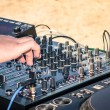Hand of a deejay playing music on professional mixing controller — Stock Photo #44560793