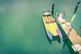 Multicolored speedboat ready to sail at wooden pier - Retro nost — Stock Photo