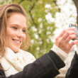 Beautiful happy young woman taking a selfie with a modern cell phone in the park - Lifestyle of a single blonde girl smiling on a smartphone outdoors — Stock Photo #45097135