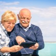 Senior happy couple having fun with a tablet at the beach - Portrait of man and woman interacting with modern technology — Stock Photo