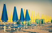 Umbrellas and sunbeds at Rimini Beach Italy - Vintage retro nostalgic filtered look of the world famous italian Riviera — Stock Photo