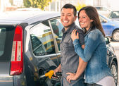 Happy couple at fuel station pumping gasoline at gas pump. Portrait of young man and woman of man filling modern car at gasoline tank — Stock Photo