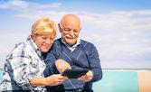 Senior glückliches paar, die spaß mit einem grafiktablett am strand - porträt von mann und frau, die interaktion mit moderner technik — Stockfoto