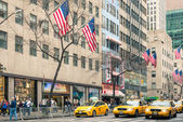 "NEW YORK - DECEMBER 22, 2013: yellow taxicabs and american flags on the 5th Avenue, named ""The most expensive street in the world"" at the crossroad with West 48th Street in Midtown Manhattan. — Zdjęcie stockowe"