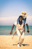 Young couple playing at the beach having fun with a piggyback jump - Happy mixed race man and woman at the beginning of a love story — Stock Photo