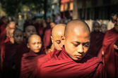 AMARAPURA, MYANMAR - FEBRUARY 10, 2014: young buddhist novices walk to collect alms and offerings in the monastery of Maha Gandhayon Kyaung near Mandalay in Myanmar. — Stock Photo