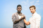 Afroamerican and caucasian men shaking hands in a modern handshake to show each other friendship and respect - Arm wrestling against racism — Stock Photo