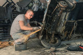 Young mechanical worker repairing an old vintage car body in messy garage — Stock Photo