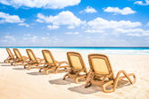 Sunbeds chaise longue at tropical empty beach and turquoise sea - Panorama of dream vacation in exclusive destination with white sand in a sunny beautiful day — Stock Photo