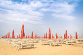 Red umbrellas and sunbeds at Rimini Beach - Italian summer overview at the beginning of the season — Stock Photo