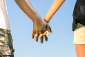 Multiracial couple walking hand in hand against a blue sky - Concept of multi ethnic love over social barriers — Stock Photo