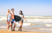 Group of young happy people on vacations at the beach holding a surf table - Best friends with girlfriends having fun in the summer with surfboard boogieboard during travel holidays — Foto Stock