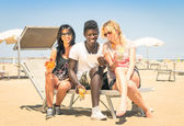 Happy multiracial girl friends drinking cocktails with tablet pc at the beach - Concept of modern vacations with girlfriends and afroamerican guy enjoying wifi internet in the summer — Foto Stock